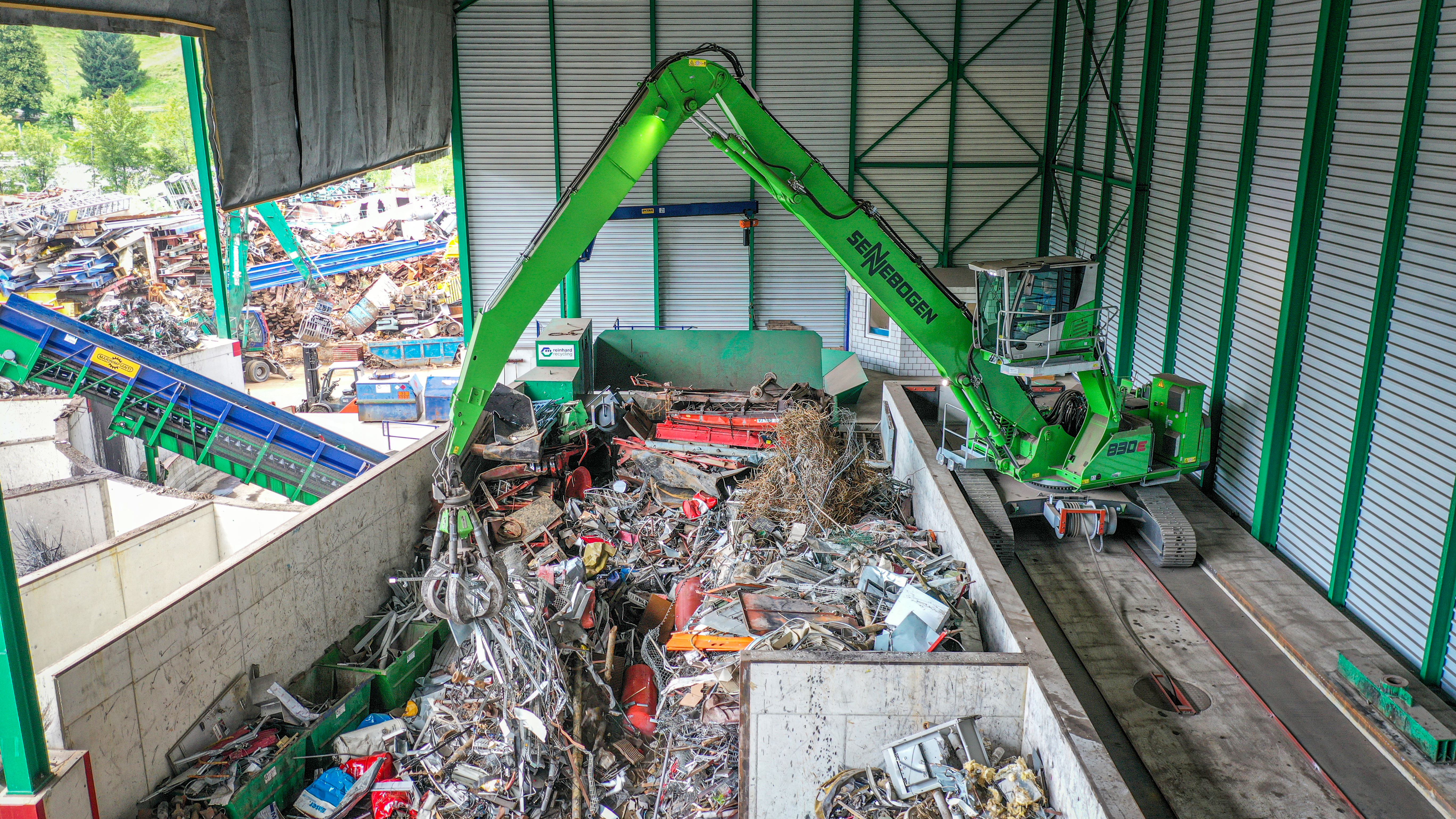 Electrically driven, environmentally friendly and effective in scrap handling: SENNEBOGEN 830 E material handler in the tracked version loads the shear with 17 m equipment in a partially open hall
