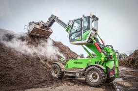 The SENNEBOGEN 355 E telehandler makes it easy to stack up high layers of bark mulch.