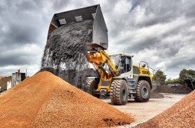 An L 556 XPower® with industrial kinematics and high dump bucket loading soil and substrate.