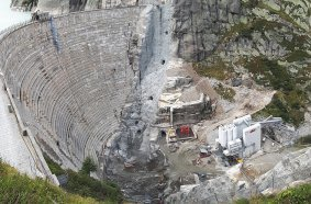 Short distances: the new double-curved arch structure is being built directly in front of the existing dam. The different recipes from the SBM mixing systems can be processed immediately using a crane bucket.