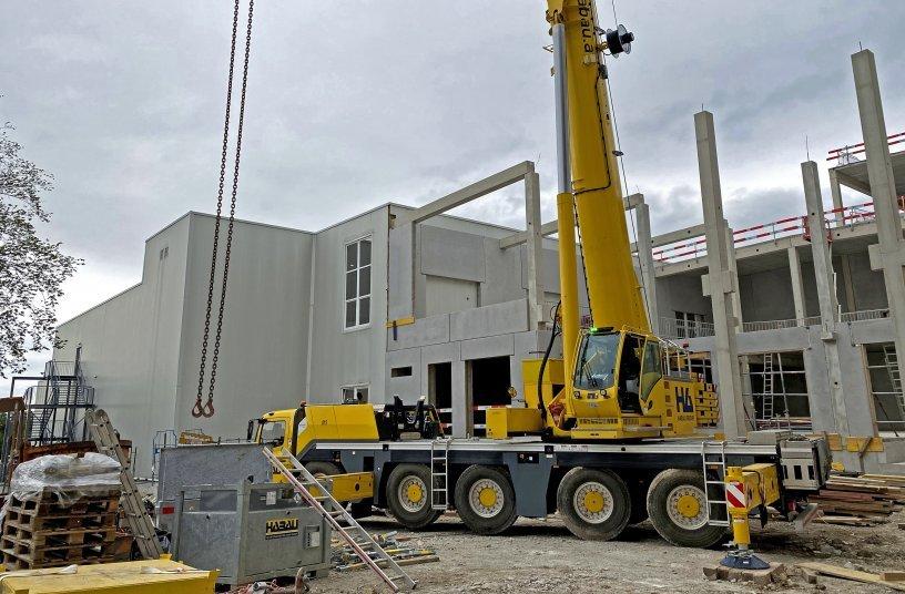 Grove GMK5150L von HABAU auf einer Baustelle in Österreich beim Einheben von Stützen, Trägern sowie Wand- und Deckenelementen im Jahr 2020.