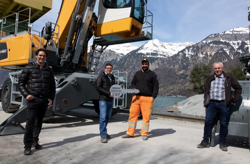 Impressive backdrop: The key to the Liebherr material handler was handed over at the harbour of Aarekies Brienz AG on Lake Brienz. From left to right: Reto Studer (Liebherr-Baumaschinen AG), Dominik Ghelma (Ghelma Group), Kaspar Thöni (Aarekies Brienz AG) and Hans Ulrich Kern (Liebherr-Baumaschinen AG).