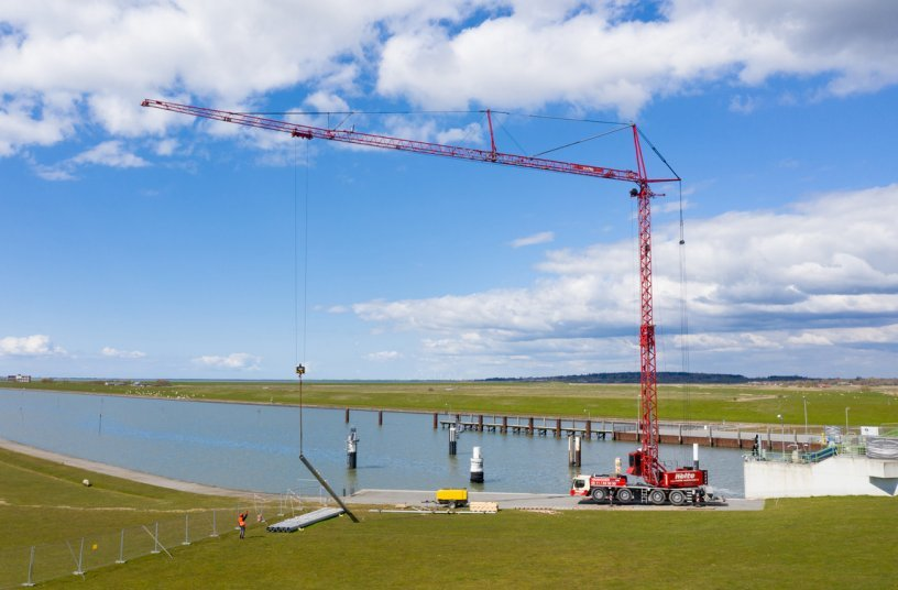 Super-sized posts: Around 150 posts had to be lifted into the water by the crane in order to assemble stop gates for draining and isolating the barrage. Divers awaited the mighty posts on the riverbed. <br> Image source: Liebherr-Werk Biberach GmbH