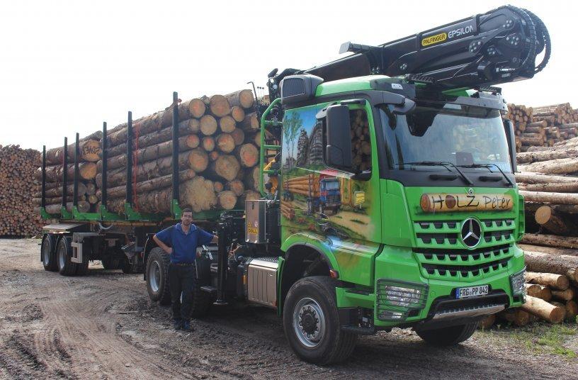 Fahrer Johann Schiller mit dem Jubiläumsfahrzeug von Holz-Peter: Arocs 6x6 mit Schemel-Sattelauflieger DOLL LOGO 20. <br> Bildquelle: DOLL Fahrzeugbau GmbH