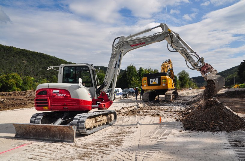 An eight-ton excavator prepares the site for the larger excavator fitted with the KSI mixing attachment. Removing some surface material along the line of the diaphragm wall prevents binder solution with cement from flowing away from the working area. <br> Image source: KEMROC