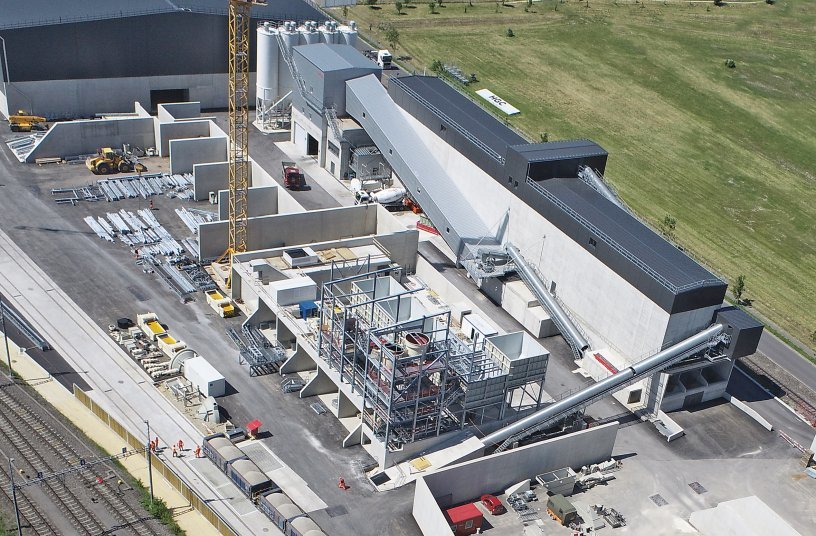 The BGO complex is easily accessible directly on the passing Cantonal road and is supplied via the bunker extractors for trucks and block trains at the track access. <br> Image source: SBM Mineral Processing GmbH